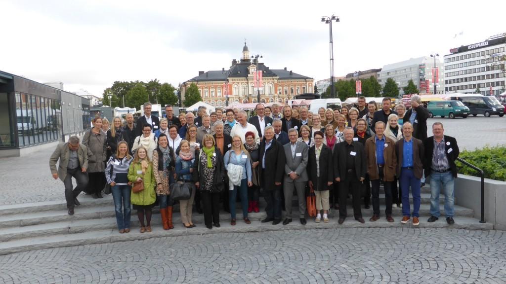 Konferenssin osanottajia Kuopion torilla. Taustalla tapahtumapaikka, Kuopion kaupungintalo